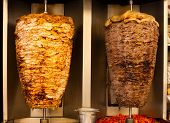 image of shawarma  - Delicious slabs of skewered fast food shawerma chicken and lamb meat turn on a spit - JPG