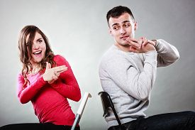 picture of fool  - Happy couple having fun and fooling around pretending their hands fingers are guns - JPG