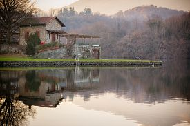 pic of mansion  - A small mansion on the Alpine lake of Sirio with grass garden during autumn with calm water and reflections - JPG