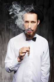 picture of smoke  - Attractive young man with beard is smoking cigar - JPG