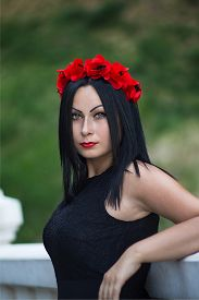 picture of gothic hair  - Portrait of black haired gothic woman in the chaplet of red flowers and black dress - JPG