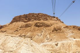 stock photo of masada  - The historic landmark of the Masada plateau is eaily reached by a gondola using overhead cables that stretch from the base to the top. The alternative hiking trail winds up the mountain at the right.