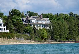 image of mansion  - A lakefront mansion behind trees in Harbor Springs - JPG
