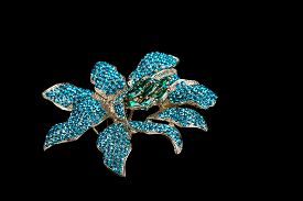 foto of brooch  - Colorful gem brooch brooch in the form of a flower on black background - JPG