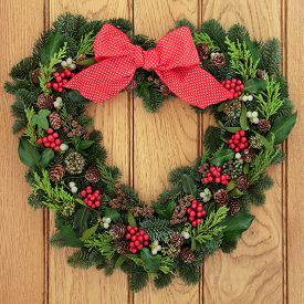 stock photo of greenery  - Christmas and winter heart shaped wreath with holly - JPG
