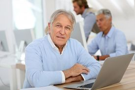 picture of senior class  - Portrait of senior man working on laptop - JPG