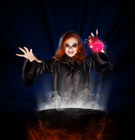 picture of cauldron  - Young witch with potion and cauldron on blue rays background - JPG