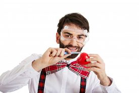 picture of scalpel  - Determined man wearing suspenders cutting heart model with scalpel - JPG