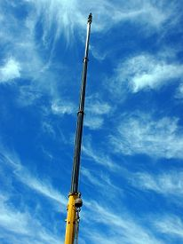 image of boom-truck  - Upward view on the boom of a crane against the blue sky with white cirrus clouds - JPG