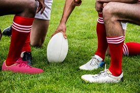 pic of huddle  - Rugby players in huddle with ball at the park - JPG