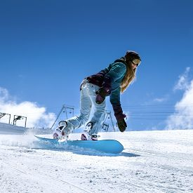 image of snowboarding  - Young woman snowboarder in motion on snowboard in mountains on the slopes - JPG