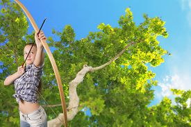 picture of archery  - Teen girl practicing archery with green tree in background - JPG