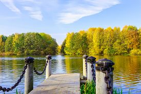foto of dock a lake  - Landscape with Stone Dock Colourful Trees at Lake and Cloudy blue Sky at Sunny Day in Autumn - JPG