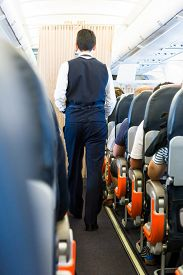 stock photo of cabin crew  - Airplane interior. Cabin crew walking down the aisle. ** Note: Visible grain at 100%, best at smaller sizes - JPG