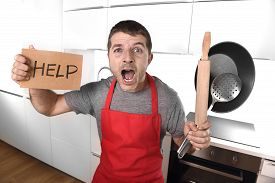 stock photo of panic  - funny 30s Caucasian man holding pan and rolling pin wearing red apron at home kitchen asking for help unable to cook showing and screaming in cooking panic with funny face expression - JPG