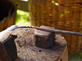 stock photo of anvil  - Blacksmith working the old traditional way on metal on an anvil - JPG