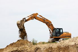 image of excavator  - Excavator loader machine during earthmoving works outdoors at construction site focus on excavator