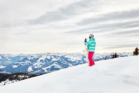 stock photo of snowboarding  - Back view of female snowboarder wearing colorful helmet - JPG