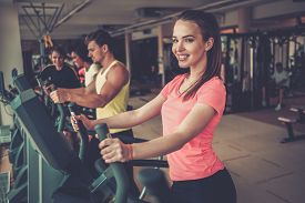 picture of cardio exercise  - People exercising on a cardio training machines in a gym - JPG