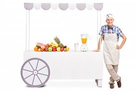 picture of jerks  - Senior soda jerk standing next to a stall with a juicer and a bunch of fresh fruits on it isolated on white background - JPG