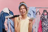 Unhappy Female Going To Cry While Standing In Shopping Centre, Holding In One Hand Hangers With Clot poster