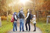 adventure, travel, tourism, hike and people concept - happy family walking with backpacks in woods a poster