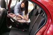 Mother fastening sleeping baby to child safety seat inside of car poster