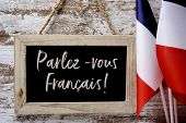 a wooden-framed chalkboard with the question parlez-vous francais? do you speak french? written in F poster