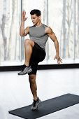 Fit, Athletic Male Model In Sportswear Doing Strength Exercise With Knee Up In Gym, Isolated On A Bi poster