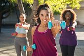 Portrait of young curvy woman with friends exercising with dumbbells. Group of three multiethnic gir poster