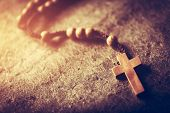 Wooden rosary with cross on stone background. Christian religion. Catholic faith. Prayer. poster
