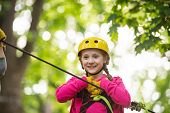 Happy Little Child Climbing On A Rope Playground Outdoor. Cute Child In Climbing Safety Equipment In poster