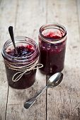 Two jars of fresh cherry and wild berries  homemade jam in jar on rustic wooden background. Healthy  poster