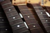 Many guitar necks aligned. Rosewood and ebony finger board electric guitar necks made from maple. poster