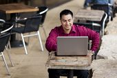 image of telecommuting  - Stock photo of a well dressed Hispanic businessman looking down at a laptop while telecommuting from an internet cafe - JPG