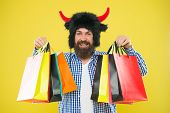 Shopping For Pleasure. Bearded Man Smiling With Shopping Bags. Happy Hipster In Bull Horns Hat Holdi poster