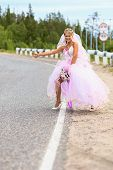 Bride Hitching On A Road