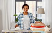 housework, laundry and housekeeping concept - happy african american woman with ironed linen on iron poster