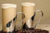 picture of frappe  - two mugs of iced coffee frappe with coffee beans on a wooden table - JPG