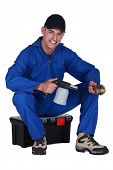Man sitting on a toolbox with a blowtorch poster
