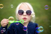 A Cute Little Girl Child In Sunglasses Is Blowing Bubbles Outside On A Summer Day. poster