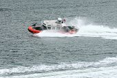 stock photo of coast guard  - Coast Guard boat cutting through water in harbor - JPG