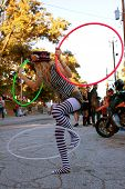 Female Street Performer Entertains With Three Hula Hoops