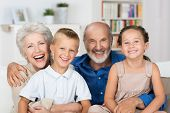 foto of grandparent child  - Happy young boy and girl with their laughing grandparents smiling at the camera as they pose together indoors - JPG