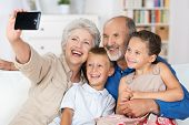 stock photo of grandparent child  - Grandparents and grandchildren sitting together in a close group on a sofa laughing and doing a self portrait with a hand held camera on a mobile phone - JPG