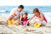 stock photo of family fun  - young happy family on the beach  - JPG