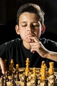 foto of 11 year old  - An 11 year old boy thinking about his next move during a chess game - JPG