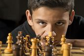 stock photo of 11 year old  - An 11 year old boy staring down his opponent during a game of chess - JPG