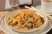 pic of lo mein  - Closeup of a cup of beef lo mein with a cup of tea  - JPG