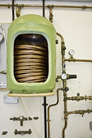 stock photo of hot water  - Exposed copper hot water cylinder with exposed heat exchanger - JPG